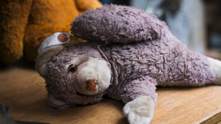A worn out stuffed animal on a wooden table
