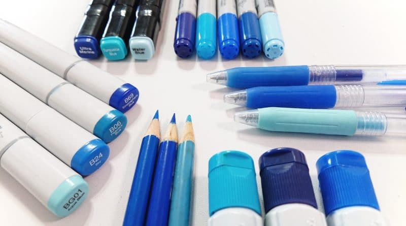 different types of blue coloured pens, pencils, and markers on a white table