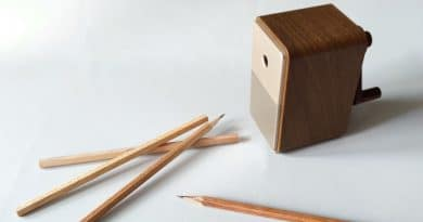 A wooden pencil sharpener and a few pencils on the desk