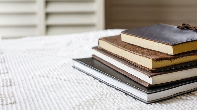 a pile of books with covers on a table
