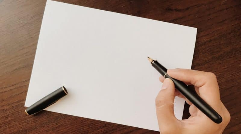holding ballpoint pen with a blank paper on the table