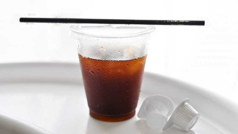 A straw on a plastic cup filled with ice coffee