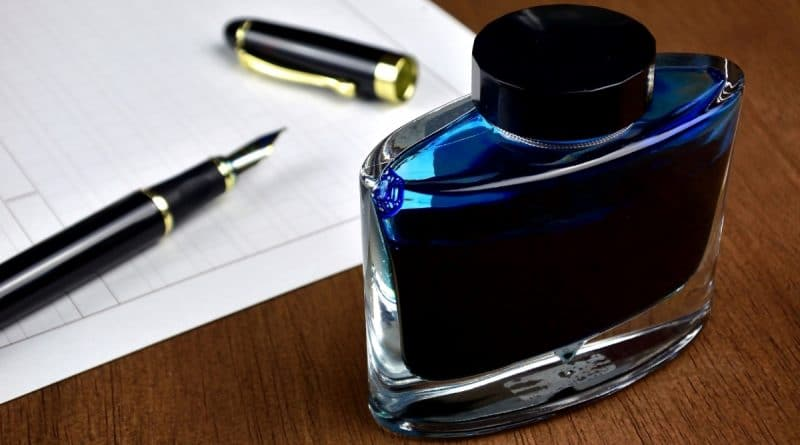 fountain pen with an ink bottle and paper